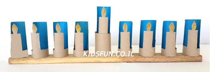 החומרים: 10 גלילי נייר טואלט ריקים עיפרון צבע אקריליק/גואש כחול (או כל צבע אחר לטעמכם) מכחול מספריים דבק אפשרות: נצנצים זהובים או צבע אקריליק/גואש כתום/אדום/צהוב קורת עץ מלבנית […]